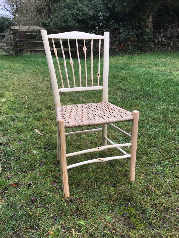 7 spindle back dining chair with knotty features and paper rush seat