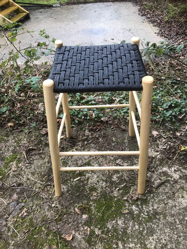 front view of a sloping seated perching stool with black danish cord seat