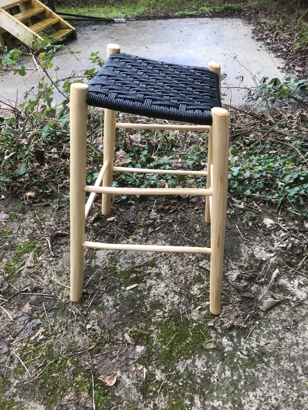 side view of a sloping seated perching stool with black danish cord seat