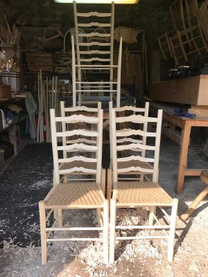 Four Sweetheart Ladderback chairs with one unfinished carver chairs on a workbench